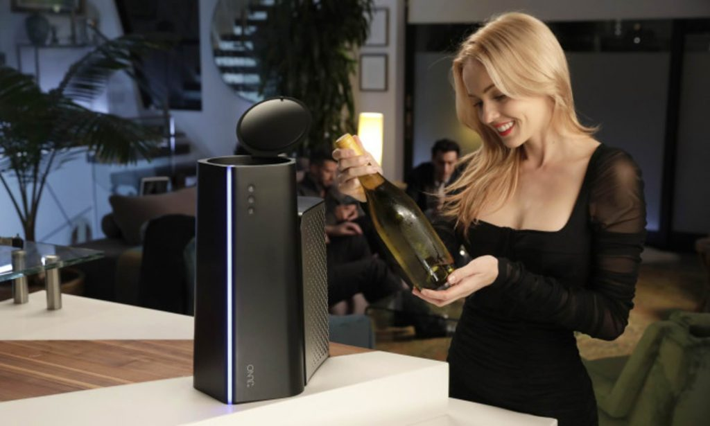 """Woman holding a bottle of wine next to the Juno """"reverse microwave"""""""